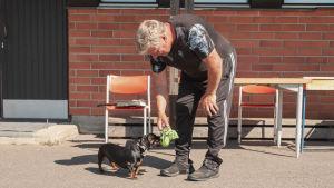 Mies on kumartunut koiran talutushihna kädessään ja pieni mäytäkoira edessään.