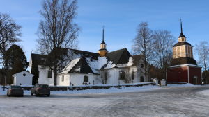 En vit kyrka med svart tak. Två bilar står på gården.