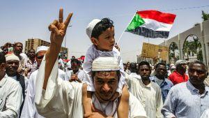 En sudanesisk man med en liten pojke på axlarna under en demonstration i Khartoum på fredagen 12.4.2019.