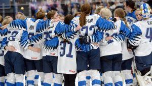Finlands damlandslagsspelare i ishockey håller om varandra.