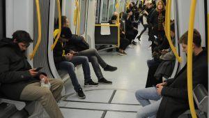 Passagerar på tåg kollar sina mobiltelefoner.
