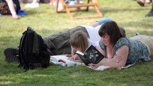 Mor och dotter ligger och läser i gräset.