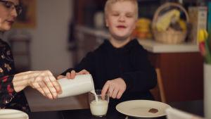 Rafael kokeilee sormellaan, onko maitomuki jo täynnä.