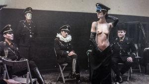 Natsit istuvat ja katselevat puolialastonta naista. Kuva elokuvasta Yöportieri.