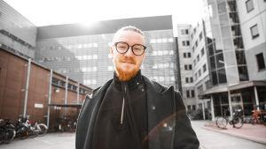 Jurek Reunamäki seisoo toimistorakennuksen edessä, taustalla polkupyöräparkki. Hymyilee tummissa vaatteissaan ja silmälaseissaan, aurinko heijastuu takaa. Kuva rajattu kyynärpäistä alaspäin.