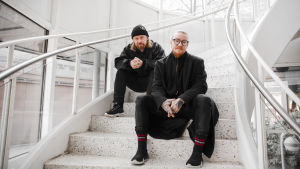 Hank Solo ja Jurek istuvat valkoisilla toimistoportailla ja katsovat suoraan kameraan. Molemmat ovat pukeutuneet kokomustaan, streetwear-tyyppiseen vaatetukseen.