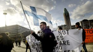 Asylsökande demonstrerar för en humanare asylpolitik med Finlands flagga i handen på Järnvägstorget i Helsingfors.