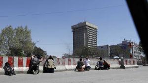 Fotografer i skydd bakom betonghinder. Ett attentat pågår i höghuset i bakgrunden.
