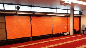 Den oranga väggen i bönerummet visar riktningen mot Mecka, dit bönerna riktas.