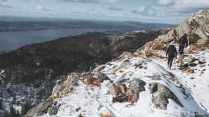 Elin och Andreas vandrar längs med en snötäckt stig högt uppe i fjällen.