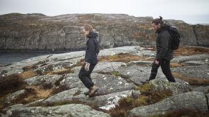 Elin och Andreas vandrar i regnet längs med en stig vid stranden.