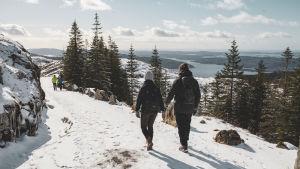 Elin och Andreas vandrar ner för Fløyfjellet längs med en bred stig, i bakgrunden syns ett vackert fjordlandskap.