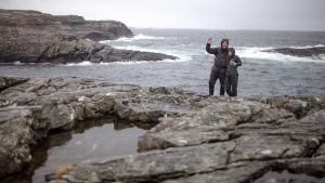 Elin och Andreas står på en klippa vid havet och vinkar.