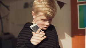 Poika pitää kännykkää kädessään, keskittyneen näköisenä, katse on alaspäin ohi kännykän.