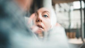 F (Fanni Sjöholm) katsoo kameraan kädessä olevan peilinpalasen kautta, josta näkyy hänen kasvonsa.