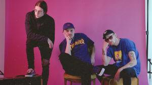 Kolmihenkinen rap-yhtye Mouhous pinkin valokuvataustan edessä. tummahiuksinen mies, jolla on mustat vaatteet ja silmälasit seisoo nojaten toisella jalallaan laatikkoon, kaksi sinipaitaista miestä istuu tylsistyneen näköisenä omaan käteensä nojaten.