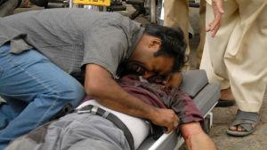 På bilden kramar en man ett av dödsoffren i moskéattacken i Lahore i Pakistan i september 2010.