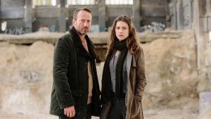 Mies ja nainen seisovat vakavannäköisinä jonkinlaisen betonisen rakennuksen sisällä, jossa näyttäisi olevan myös hiekkaa.