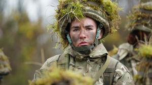 Nuori sotamies katsoo kameraan päässään kypärä, jossa on sammalta.