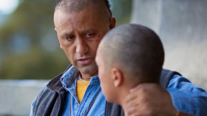 Mies ja poika istuvat vierekkäin. Mies pitää kättään pojan toisella olalla / niskassa.