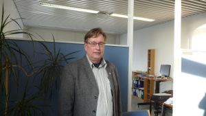Kjell Wennström. Man står i ett rum.