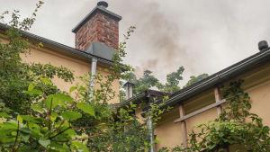 Katto ja savupiippu, josta tupruaa savua ilmaan.