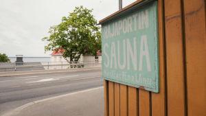 Kyltti, jossa lukee 'Rajaportin sauna'. Taustalla tie ja sen takana järvi.