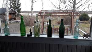 Gamla flaskor på fönsterkarm i en sommarstuga vid Djupsten i Nykarleby
