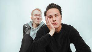 Kuumaa-yhtyeen Jonttu Luhtavaara ilveilee etualalla istuvalle Johannes Brotherukselle, joka nojaa päätään tylsistyneen näköisenä kämmeneensä. Miehet istuvat valkoisen taustan edessä.
