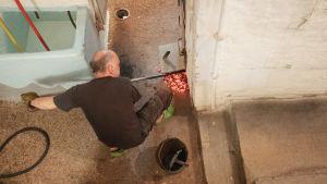 Ylhaaltä kuvattu mies poistaa hiilihangolla hiiliä lattialle suuresta kiukaasta,