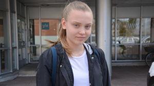 Flicka med hästsvans och läderjacka utanför Yle.