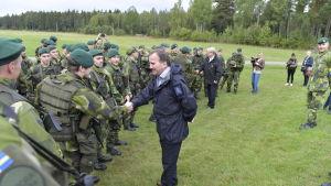 Statsminister Stefan Löfven, med försvarsminister Peter Hultqvist i bakgrunden hälsade på soldater under militärövningen Aurora  i september 2017.