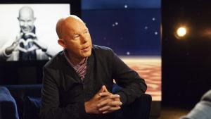 Kaj Kunnas sitter i en fåtölj i Daniel Olins tv-studio.