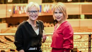 Susanna Turunen ja Annastiina Heikkilä seisovat takanaan euroopan parlamentin istuntosali.
