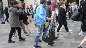 Flasksamlare med en stor svart plastsäck i folkvimlet på en gata.