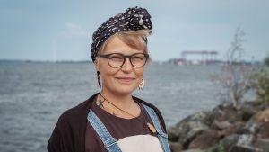 Vaaleatukkainen nainen silmälasit ja musta huivi päässä, taustalla merta