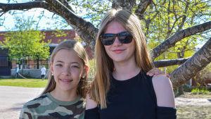 Två flickor poserar framför skola.