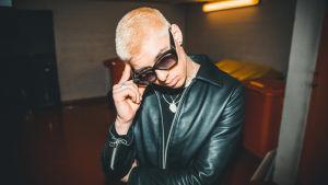 Rap-artisti Cledos lähikuvassa. Silmillään hänellä on aurinkolasit ja hän nojaa käteensä.