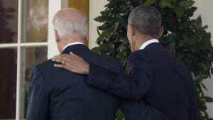 Barack Obama och Joe Biden håller vänskapligt om varandra medan de går bort från fotograferna