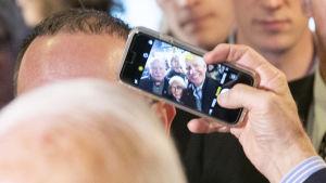 En bild på en telefonskräm som lyfts upp i luften för att ta en bild på Joe Biden tillsammans med supportrar.