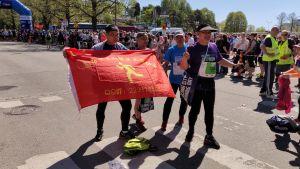Kinesiska löpare står med en flagga innan loppet