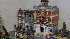 En bit av en stad byggd av legobitar. En byggnad ser ut som ett rådhus. På gatan finns en gammaldags buss av lego.