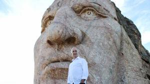 Mies seisoo ison kivinaamapatsaan edessä.