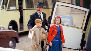 Kaksi lasta ja mies ovat menossa autolle, mies pitää toisesta lapsesta kiinni ja aukaisee auton ovea toisella kädellään ja katsoo jonnekin vasemmalle.