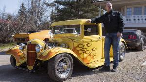 man framför gammal amerikansk bil