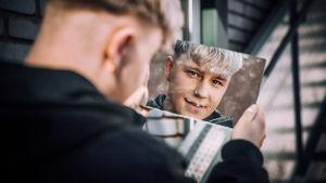Vaaleahiuksinen mies pitää käsissään peiliä, josta hänen kasvonsa heijastuvat katsojalle. Mustiinpukeutuneella miehellä on hymynkare huulillaan. Rajattu hartioista alaspäin.