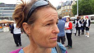 San Törnroth, en kvinna med fräknar i ansiktet och solglasögon i pannan.