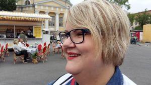 Minna Holtlund, en dam med ljust hår och glasögon med svarta skalmar.