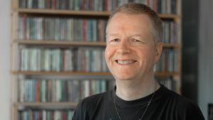 Henrik Gustafsson poserar leende framför sin cd-hylla.