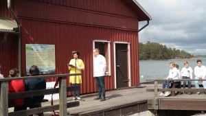 Saara Kankaanrinta och Ilkka Herlin står på en brygga på Gullkrona och håller välkomsttal vid gästhamnens öppning